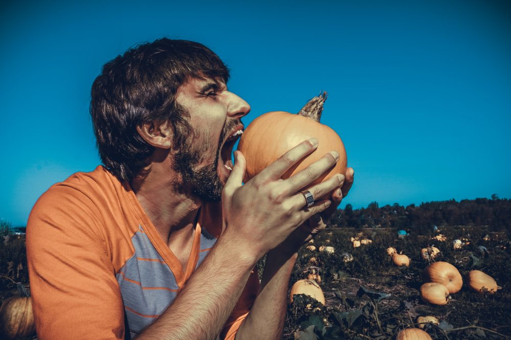 Man eating a pumpkin