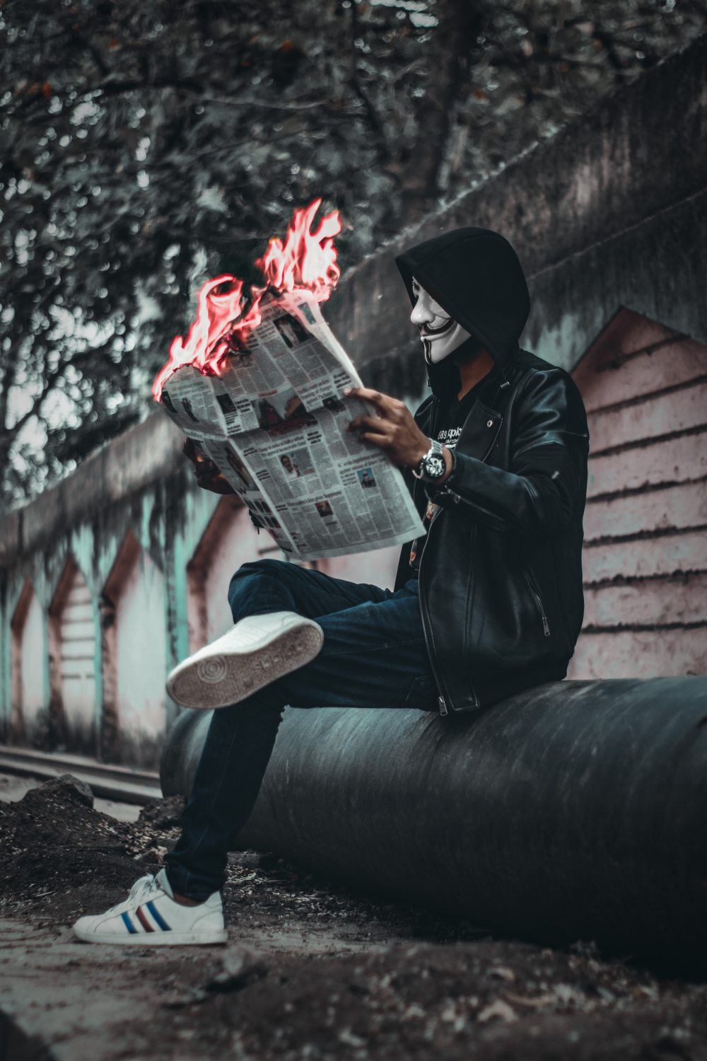 Man with mask and news paper on fire