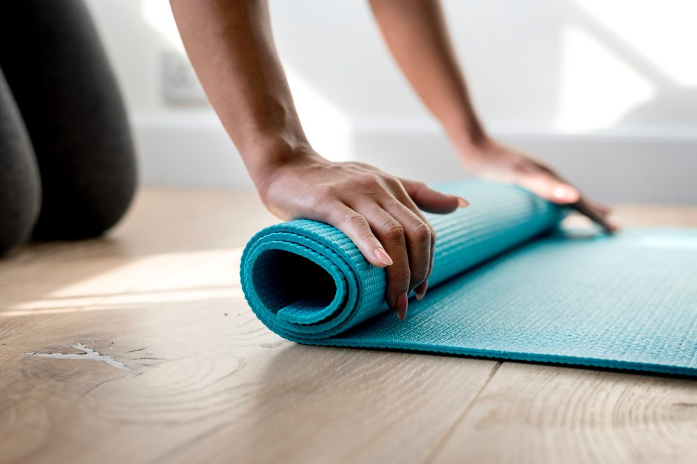 Adult rolling out a yoga mat